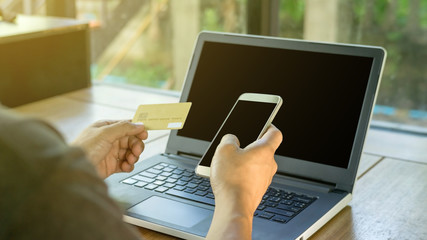 Man using a card, smartphone, and laptop on a desk, selective focus.