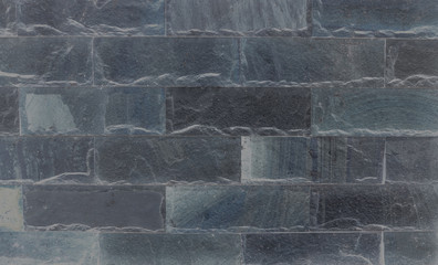 Closeup surface brick pattern at old black stone brick wall textured background