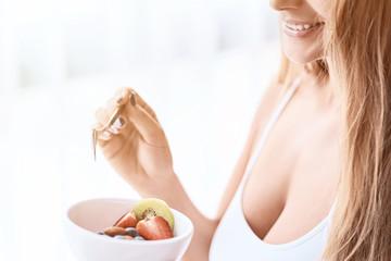 Cheerful young woman enjoying her breakfast
