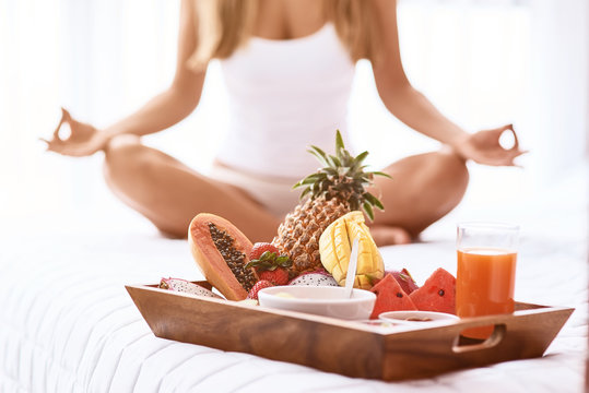 Pleasant woamn practiving yoga in bed