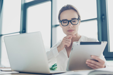 Close up portrait of serious young business woman economist in formal wear, sitting at her work place and concentrated, in front of laptop, stylish, successful, ponder, serious