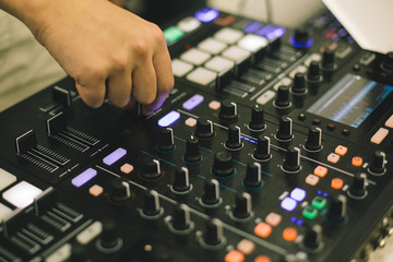 Close-up hands of soundman working with audio mixing board.