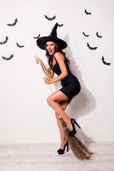 Full-length of mysterious playful, mystical gorgeous satanic bad fairy enchantress, hot figure, slim body, fashionable dark dress, shows teeth and prepared to take off on broom stick, white background