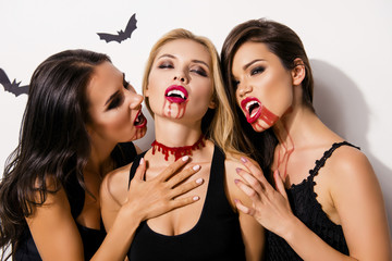 Anger, rage, death, hunger and thirst. Close up of three diabolic mysterious and paranormal mistress of the night attacking blond gothic satanic zombie, in dark dresses, on white background