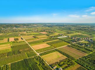 Krajobraz wiejski z lotu ptaka. Małe pola uprawne ciągnące się po horyzont.