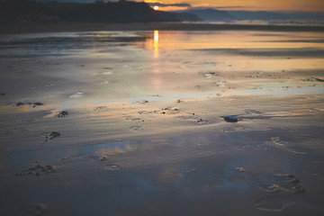 Footprints in the sand on theSopelana Beach at sunset, Bizkaia, Spain