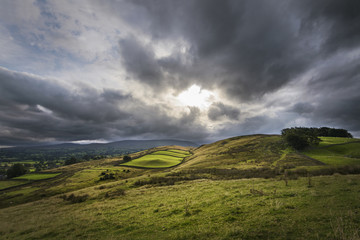 Sun breaks through clouds and shines on rural farmland England
