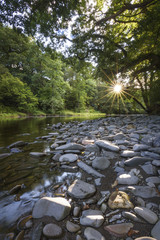 Last sunlight on river Lune with sunset star light on riverbank stones calm landscape