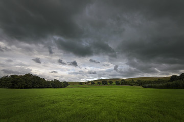 Dark clouds over green rural countryside England