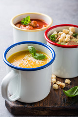 Assorted delicious homemade soups in enamel mugs with ingredients. Healthy food concept