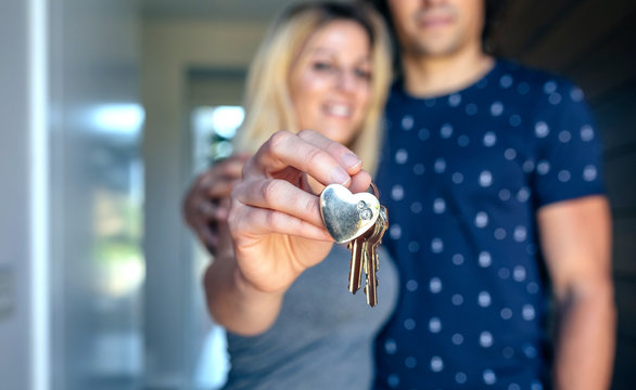 Happy couple showing the keys of their new house