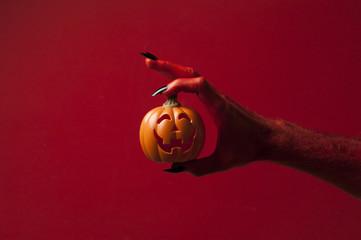 Red monster devil hand holing a pumpkin