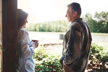 Mature couple standing on veranda, holding tin cups, smiling