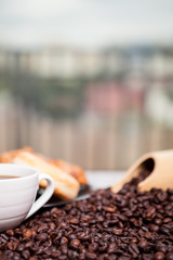 Coffee beans, sweet donut and a cup of coffee in close up photo