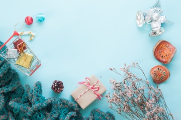 Flat lay of Christmas ornaments and gift boxes on pastel color background with copy space