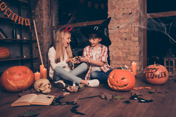 Wow! Small kids in masquerade carnival head wear, enjoying with pile of colorful dessert lots of chewy gummy sugar jelly lolipops, sittig on brown wooden floor with crossed legs, childhood, traditions Wall mural