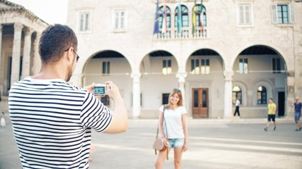 Young happy couple making photos in a tourist place on their vacation
