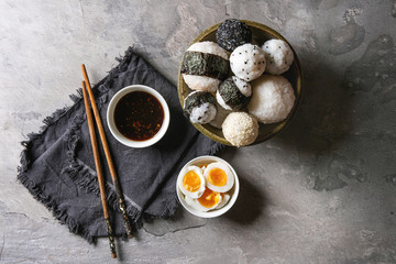 Bowl with different size rice balls with black sesame and seaweed nori, served with soft boiled eggs, soy sauce, chopsticks over gray table. Asian style dinner. Top view with space