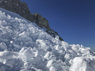 Sunlit snow mountain slope with blue sky