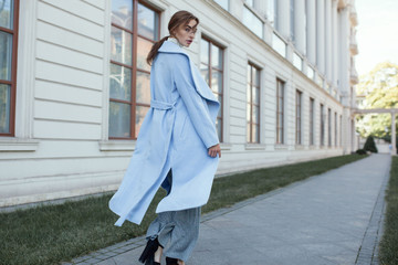 young beautiful stylish woman walking in street in blue coat, autumn fashion trend, smiling, happy. Wall mural