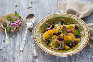 Moroccan salad of oranges with red onions, olives and cumin on a wooden table