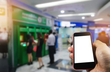 hand using smart phone isolated blank screen with blurred image of people queuing to withdraw money from ATM (Automated Teller Machine), e-banking, finance, payment and shopping online concept