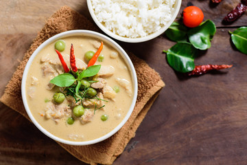 Thai food (Panaeng curry),red curry with pork and cooked rice in a bowl on wooden background.Top view of food