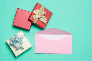 Pink envelope with blank white card and gift box for giving on color background