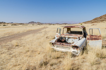 Wreck of abandoned classic car in between dry grass next to dirt road in Damaraland, Namibia, Southern Africa