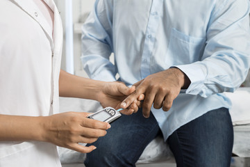 Female Doctor Examining Patient's Sugar Level With Glucometer