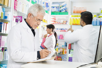 Chemist Writing On Clipboard While Coworkers Working In Pharmacy