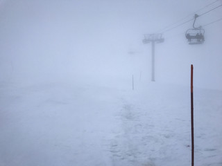 Mountain mist on ski run with red pile and ski lift fading in background Joue du Loup France