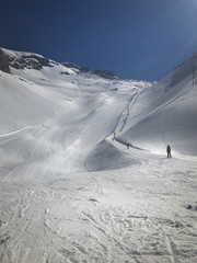Sunny black ski run with skiers going up in ski-tow Joue du Loup France