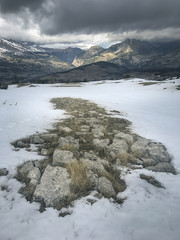 Snow melted away on rock foreground and sun lights up Alps mountain background. France