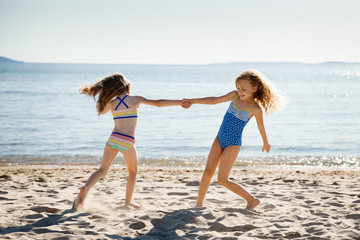 Two sisters dancing on a sandy beach
