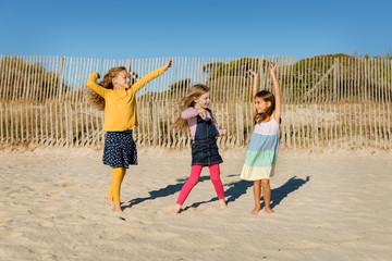 Three little girls dancing on a sandy beach