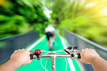 closeup of hybrid bicycle handle bar with blur background of bicycle part way in the park
