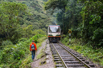 Male hiker hiking by train tracks that lead up to Aguas Calientes - the starting point for excursions to Machu Picchu, Peru