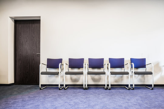 Chairs row on the blue carpet floor at the door. Waiting room in office, hospital, clinic, education or other institution. Place for waiting in line of job interview and casting. Interior concept.