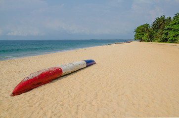 Colorful dugout fishing boat laying on deserted tropical beach at Robertsport, Liberia, West Africa