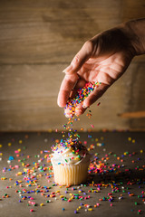 Unidentified hand pouring sprinkles on a vanilla cupcake.