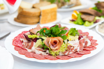 Plate of cold meats in the restaurant. Meat snacks. Smoked sausage and bacon,