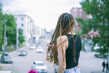 Beautiful young woman with hairdread hair dreadlocks Against the background of the city., sunny open, no face.