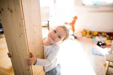 Cute little blonde girl at home at the wooden beam.