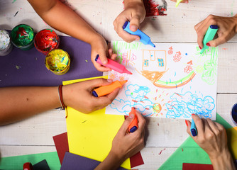 Hands hold colorful markers and draw kids illustration, top view