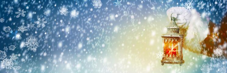Weihnachten, Hintergrund  -  Weihnachtsmann hält Laterne im Schnee