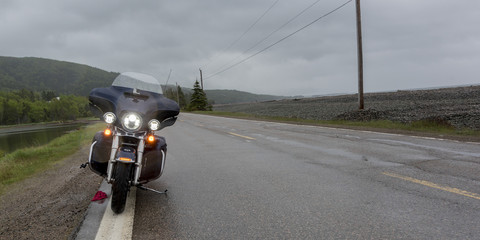 Motorcycle parked on roadside by river, Englishtown, Cape Breton Island, Nova Scotia, Canada