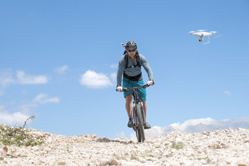 mountain biker with helmet camera followed by a drone