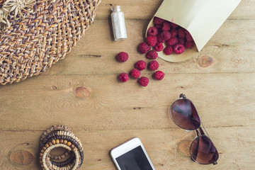 Summer holiday, vacation, relaxation concept. Raspberries, straw hat, smartphone, sunglasses from above, top view, flat lay on wooden background. Free text copy space. Summer vibes concept.