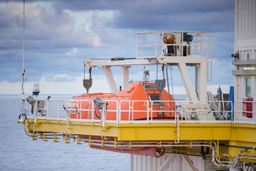 Life boat, survival craft or rescue boat at oil and gas platform for emergency evacuate at muster station.